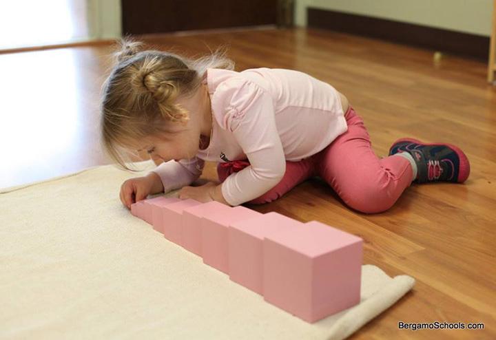 Ребёнок сосредоточенно работает с розовой башней